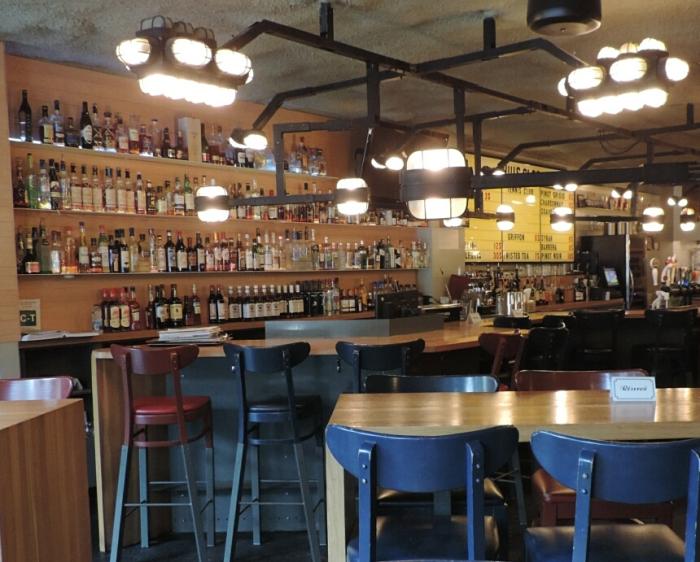 à l'avant, les chaises hautes permettent de contempler le bar, éclairé de lampes originales